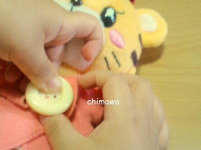 子供がこどもちゃれんじぽけっとの「はなちゃん」のボタンを留めている画像